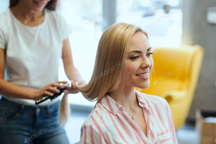 Hairdresser doing haircut for women in hairdressing salon.