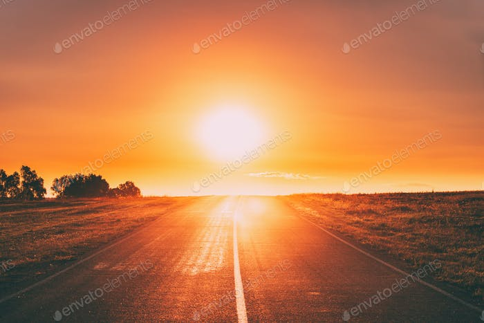 Sun Rising Above Asphalt Country Open Road In Sunny Sunrise Morn