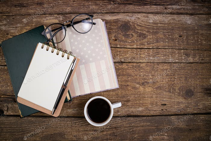 Office desk table with coffee cup, american history book, pen, notebook and eyeglasses