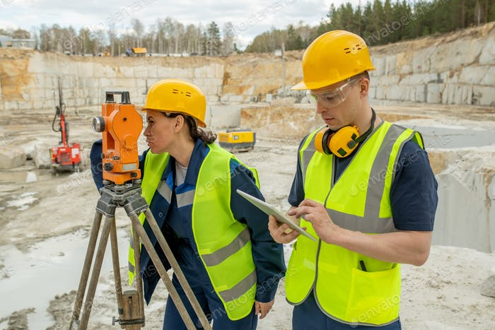 Female engineer using geodetic station by her colleague