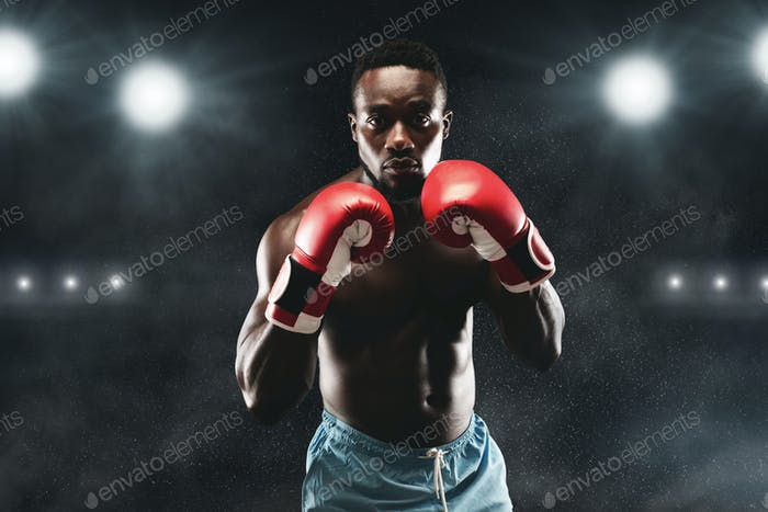 Confident black boxer standing in pose, ready to fight