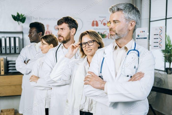 Group of multiracial doctors in lab coat standing indoors
