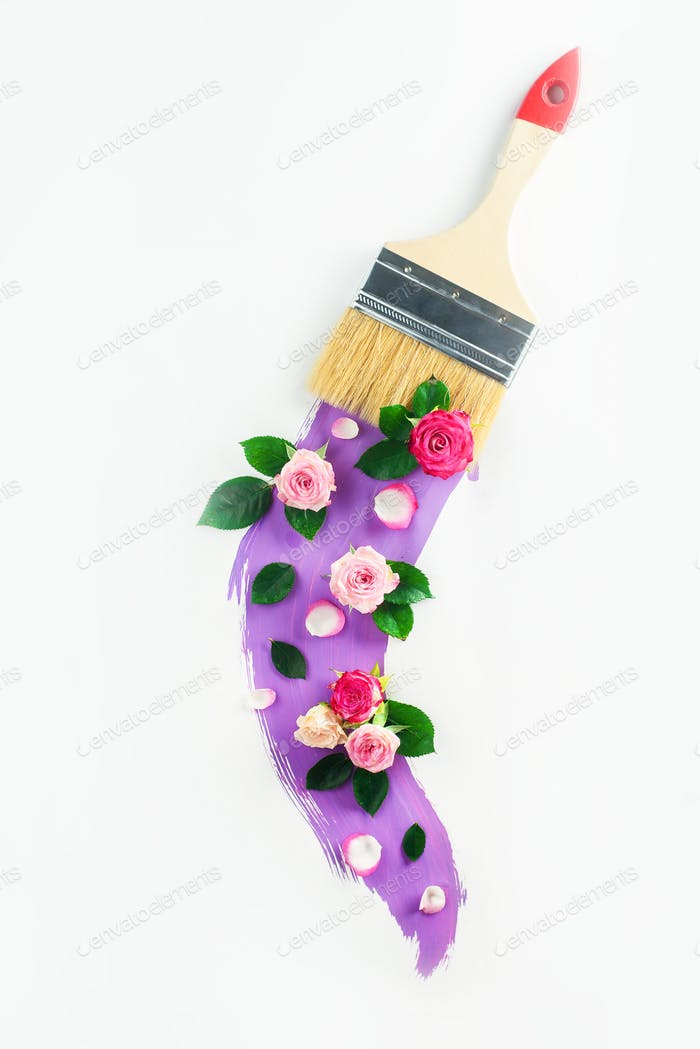 Creative spring transfiguration concept with flowers, paint brush and a swoosh of lavender color
