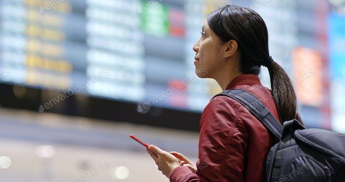 Mujer uso del teléfono móvil para comprobar el número de vuelo en el aeropuerto