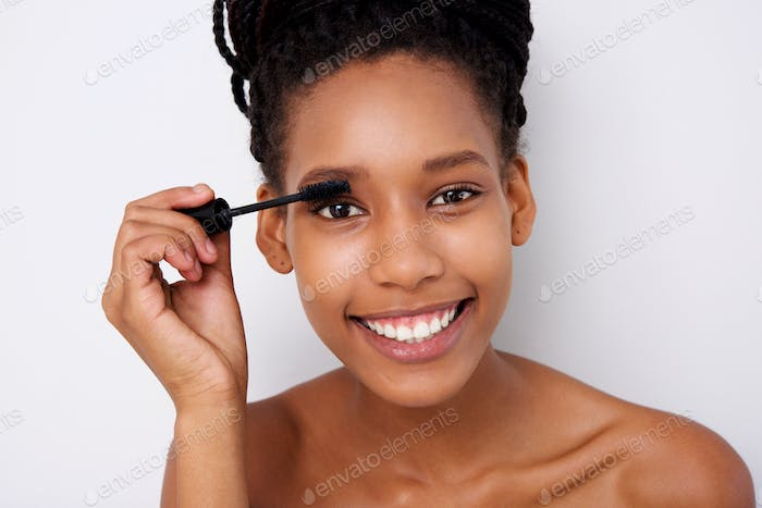 attractive african woman applying  mascara on her eyelashes