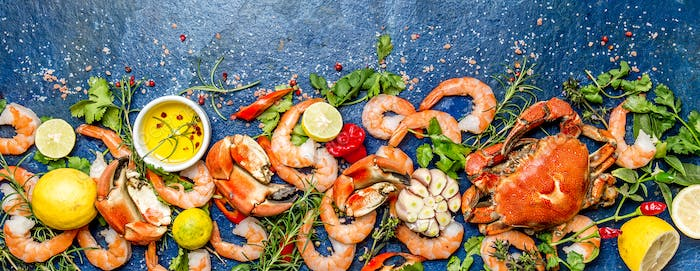 Fresh raw seafood - shrimps and crabs with herbs and spices on turquoise background