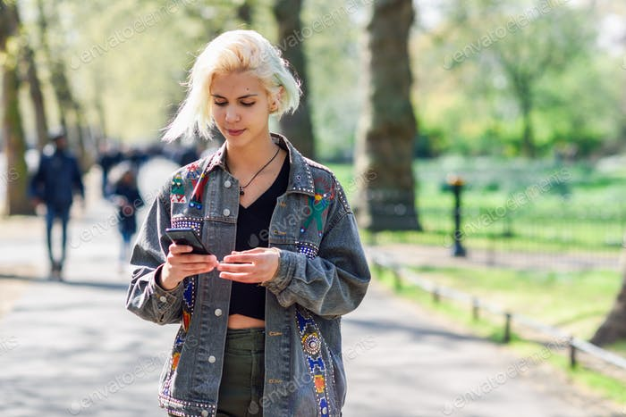 Young urban woman with modern hairstyle using smartphone walking in street in an urban park.
