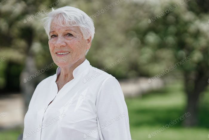 Smiling elegant elderly gray-haired woman in the white shirt is standing in a park on a warm sunny