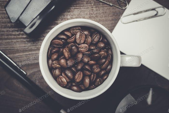 Tasse Kaffeebohnen auf Holztisch im Büro