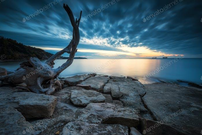 Sea sunrise at rocky beach