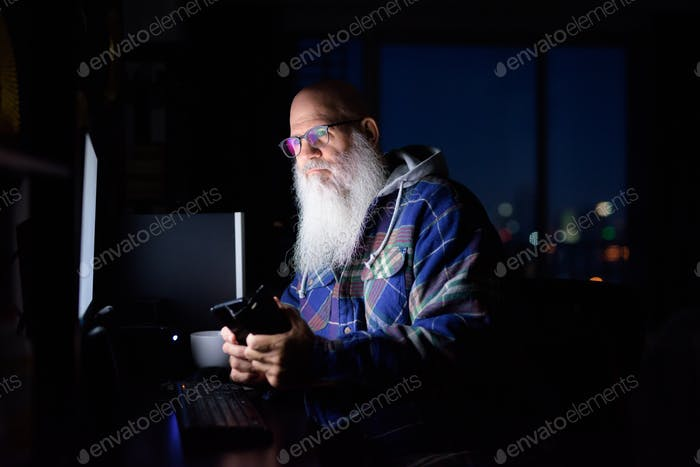 Mature bald bearded hipster man thinking and using phone at home late at night in the dark