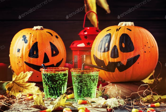 Halloween composition with festive green drink and smiling drinking pumpkins