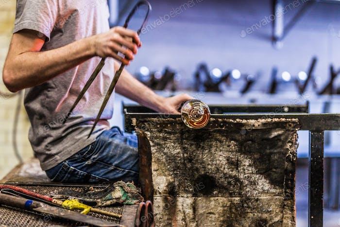 Hombre manos primer plano Trabajo en una pieza de vidrio soplado
