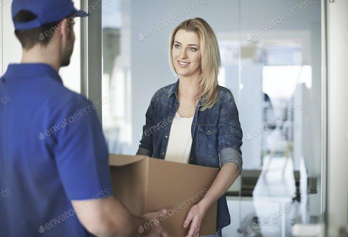 Frau bekommen ein Paket von der Lieferung Mann