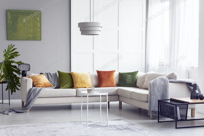 Lamp above table next to corner sofa with pillows in apartment i
