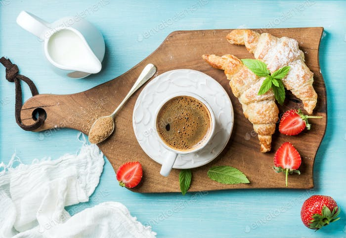 Breakfast or dessert set. Freshly baked croissants with strawberries, cup of coffee and milk