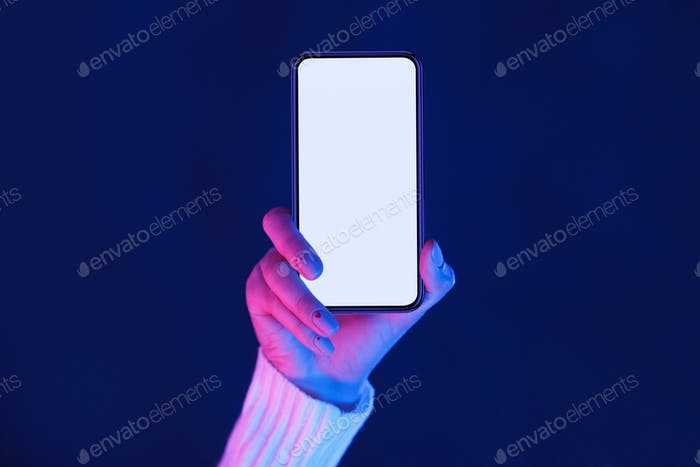 Woman's hand showing smartphone screen in neon lights