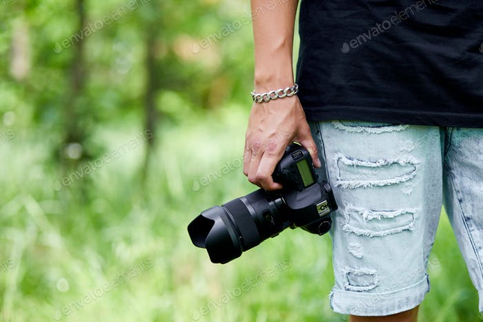 Man photographer with a photo camera in hand outdoor