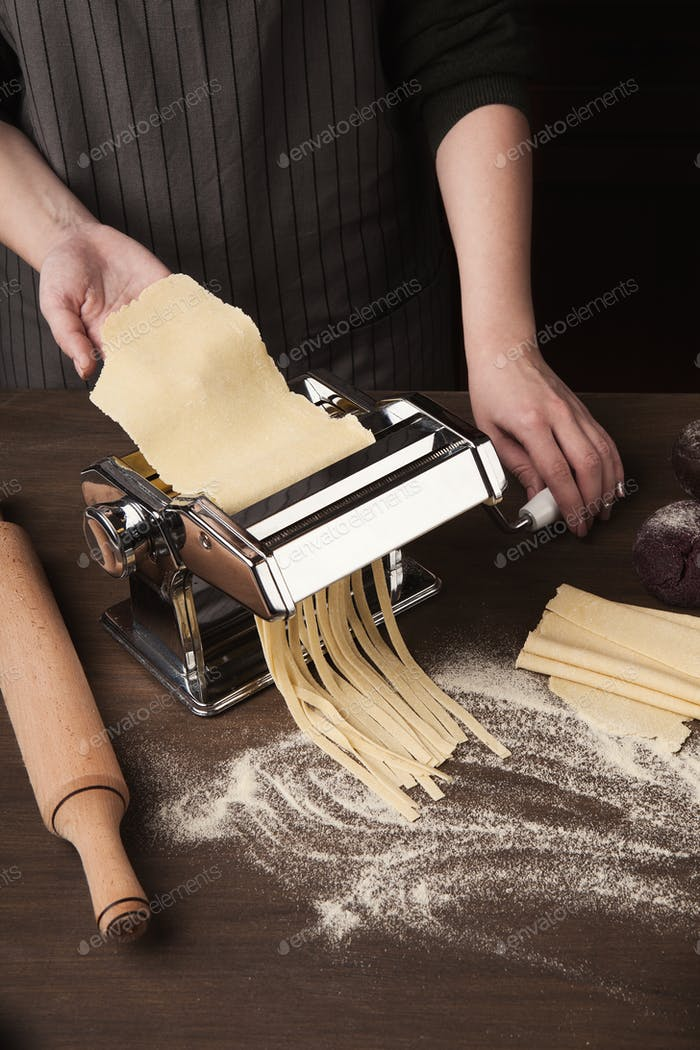 Preparing homemade fettuccine on pasta machine