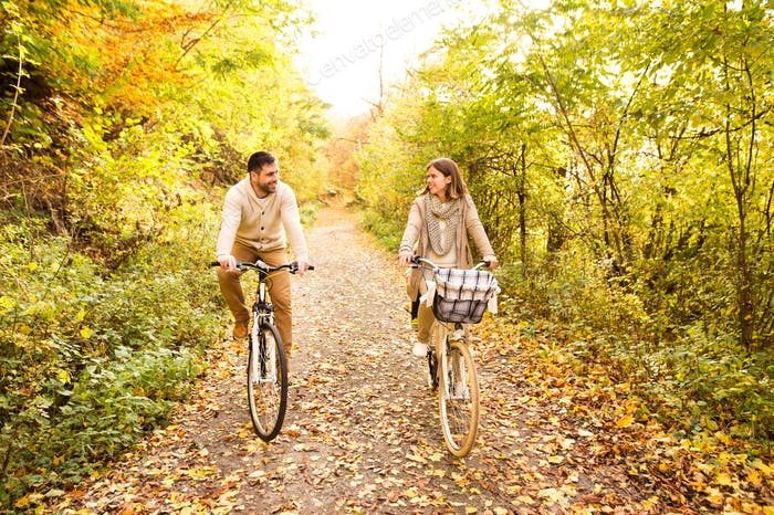 Young couple in warm clothes cycling in autumn park.