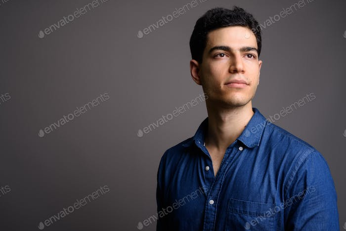 Portrait of young handsome businessman against gray background