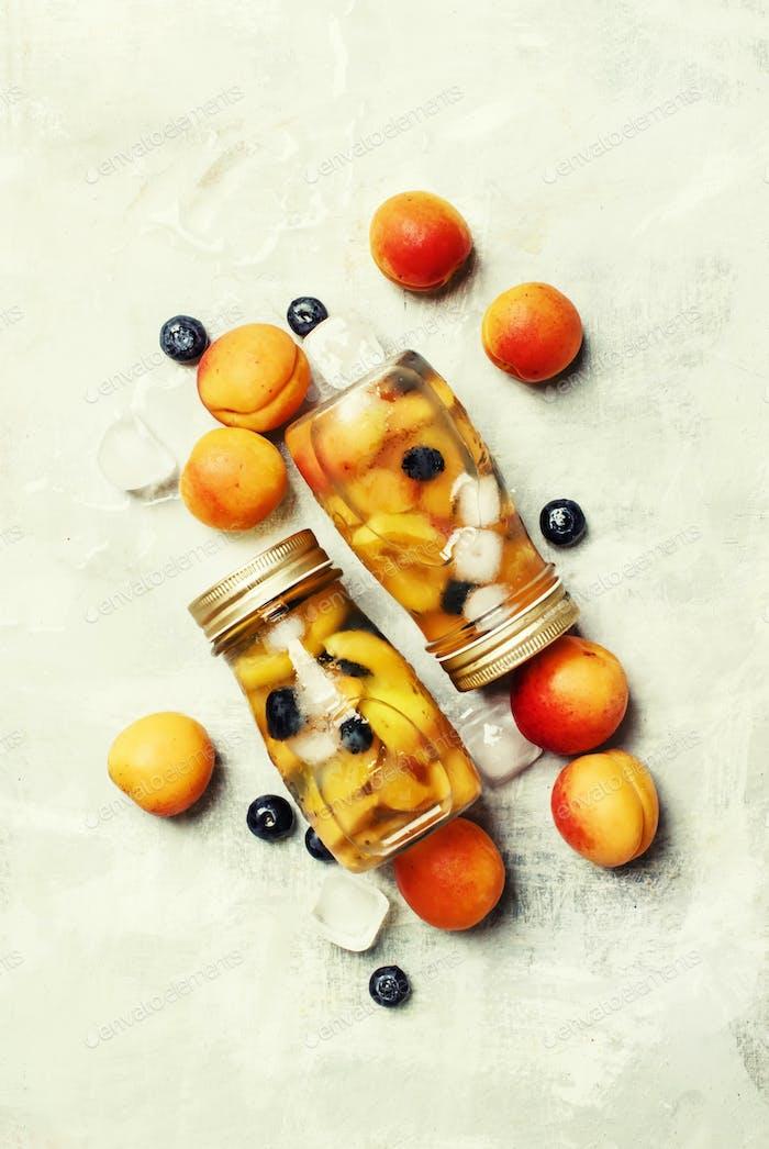 Eisiges erfrischendes Getränk mit Aprikosen, Heidelbeeren und Eis