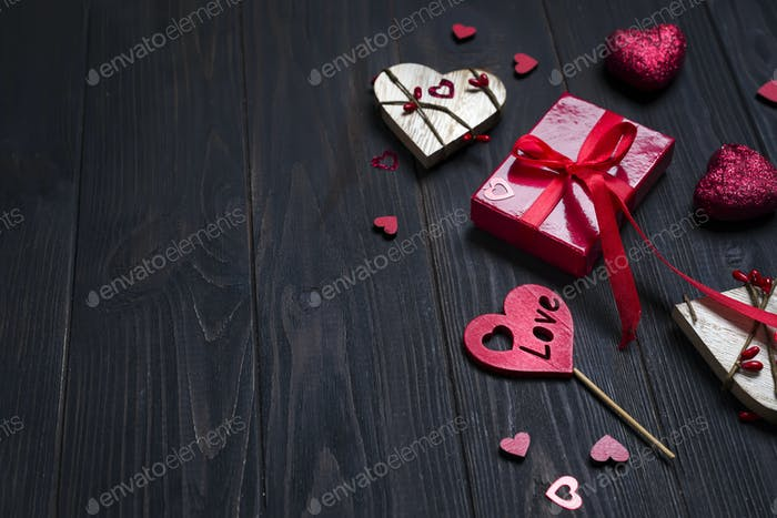 REd Holidays gift and heart on wooden background