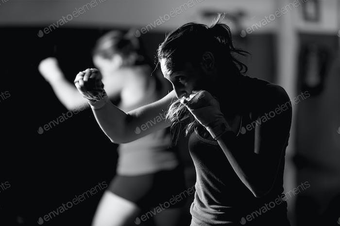 Professional young female boxer practicing strokes