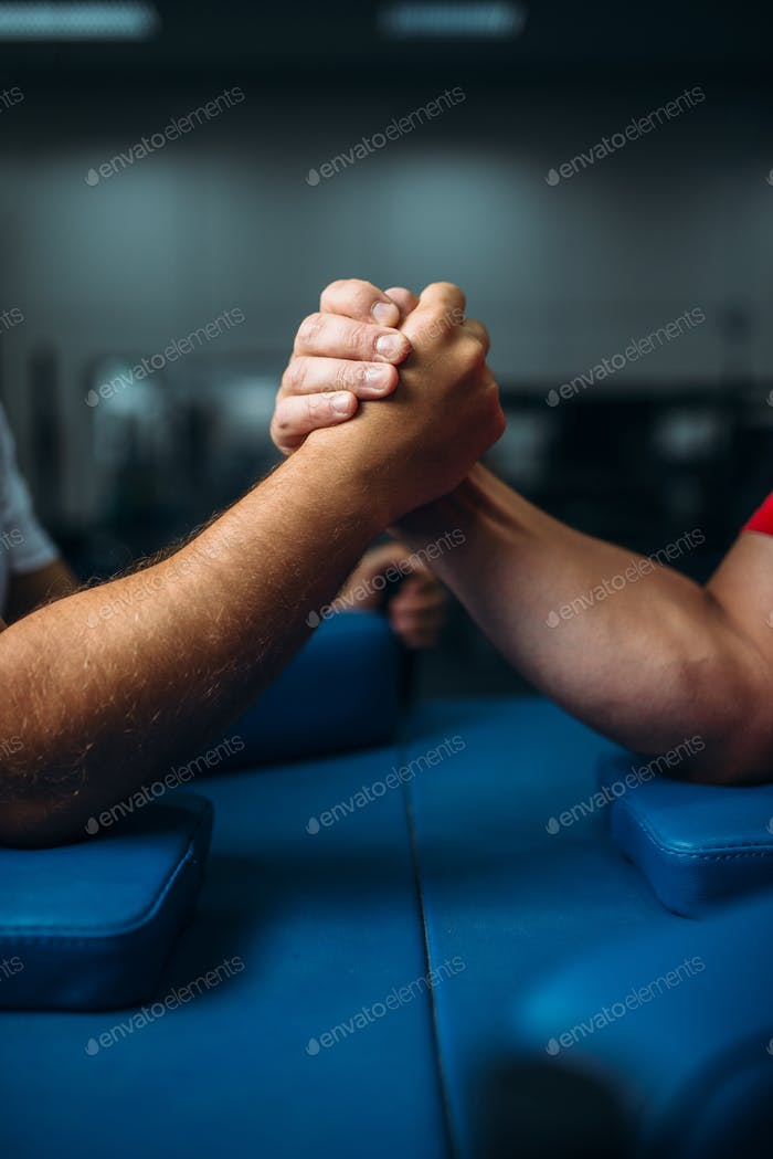 Joined male hands at the table, wrestling concept