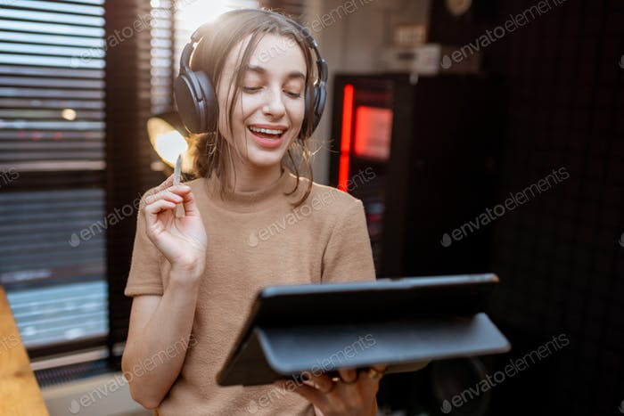 Woman in headphones with a digital tablet at home studio