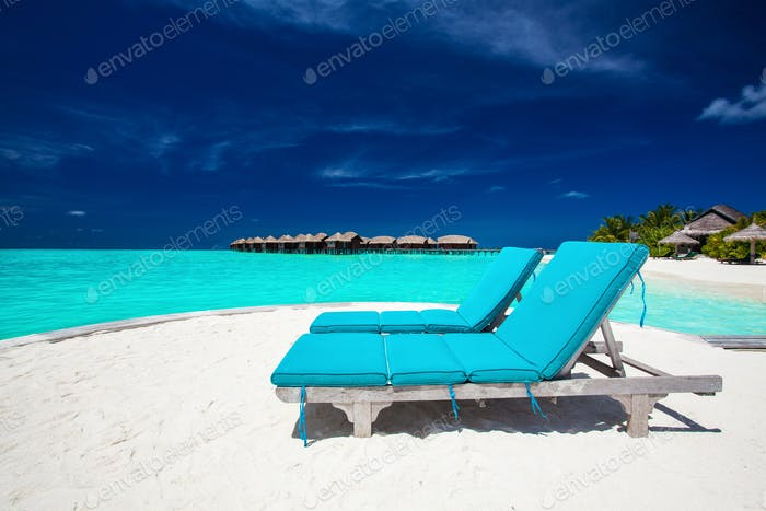 Two blue chairs on sandy island overlooking stunning tropical be