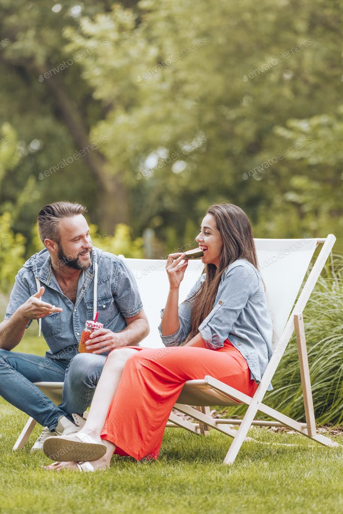 Junges Paar sitzt auf Liegestühlen im grünen Garten.
