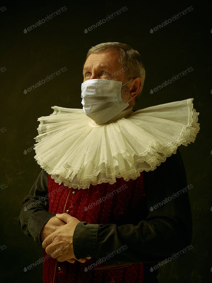 Senior man as a medieval knight on dark background wearing protective mask against coronavirus