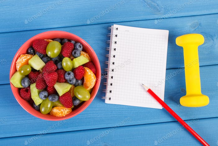 Fruit salad, dumbbells and notepad for writing notes, healthy lifestyle and nutrition concept