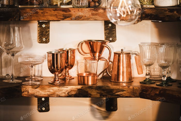 Kitchen shelves with various glassware, tumblers and utencils in daylight