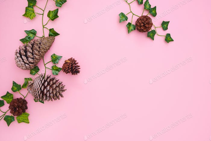 Overhead Flat Lay Autumn Banner Composed Of Ivy Leaves And Pine Cones On Pink Background