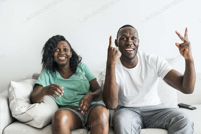 Black couple watching movie together at home