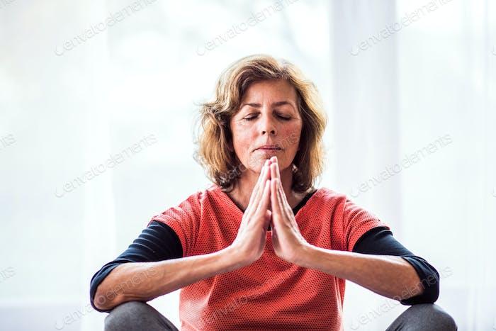 Senior woman meditating at home.