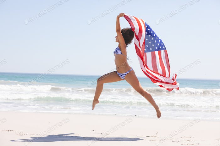 Side view of African american woman in bikini with american flag jumping on the beach