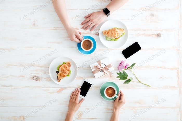 Hands of man and woman having breakfast on wooden table