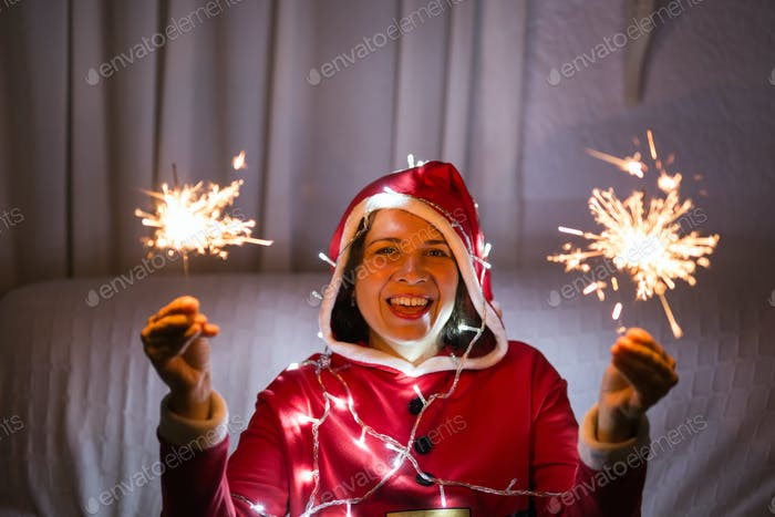 Christmas, holidays and people concept - young happy woman laughing in christmas suit with lights