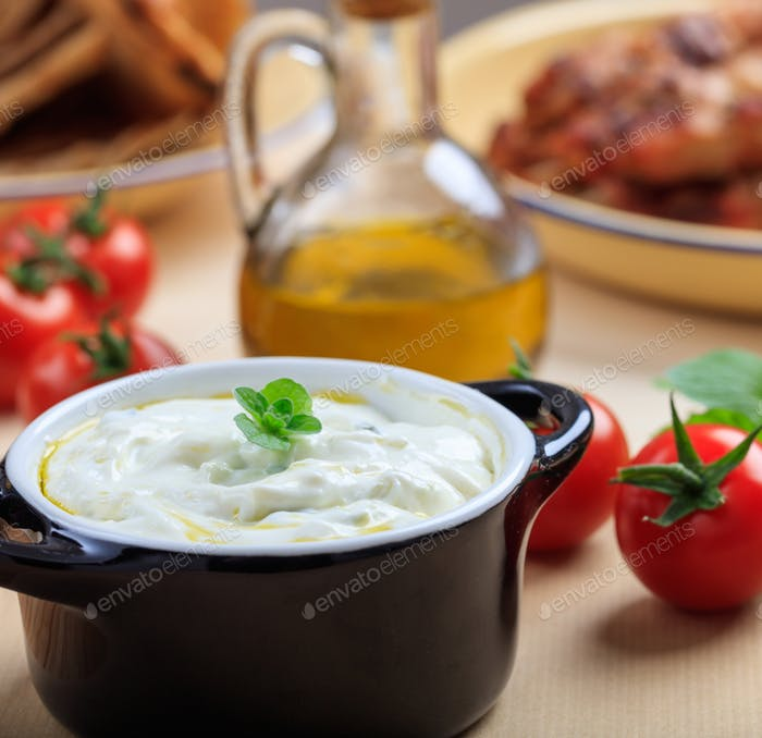 Traditional tzatziki sause in a black bowl on a table