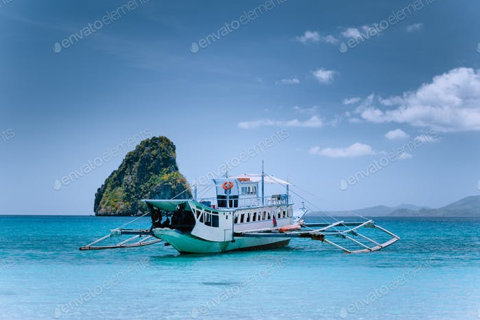 Tourism divers boat in blue cadlao lagoon on island hopping tour, El Nido, Palawan, Philippines