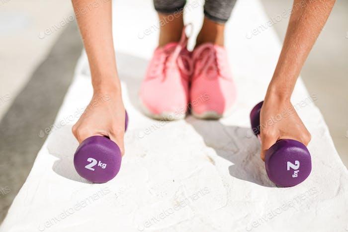 Nahaufnahme Foto von Frau Hände halten lila Hanteln und Beine in rosa Turnschuhe