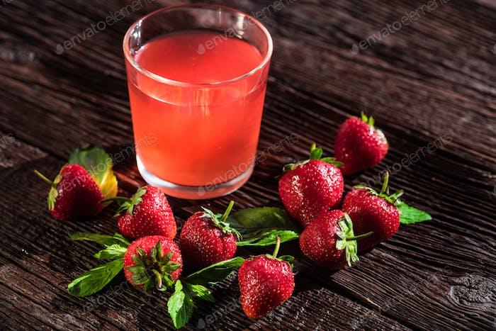 Fresh strawberries ang strawberry juice on wood