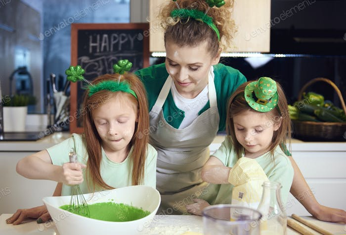 Children mixing fondant icing under mother's supervision