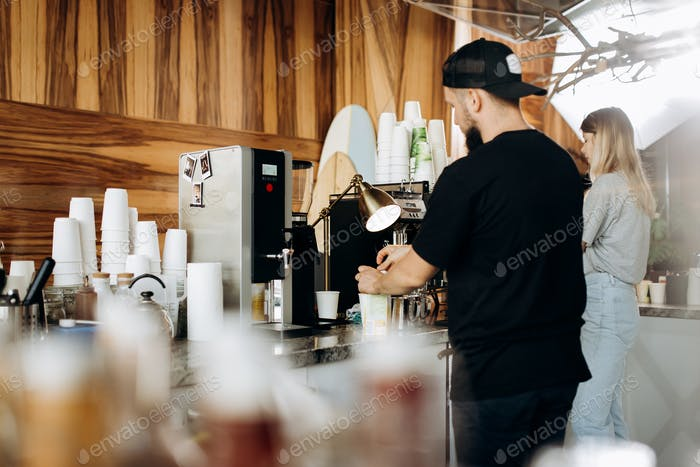 A young stylish man with beard,dressed i casual style,is cooking coffee in the expensive coffee