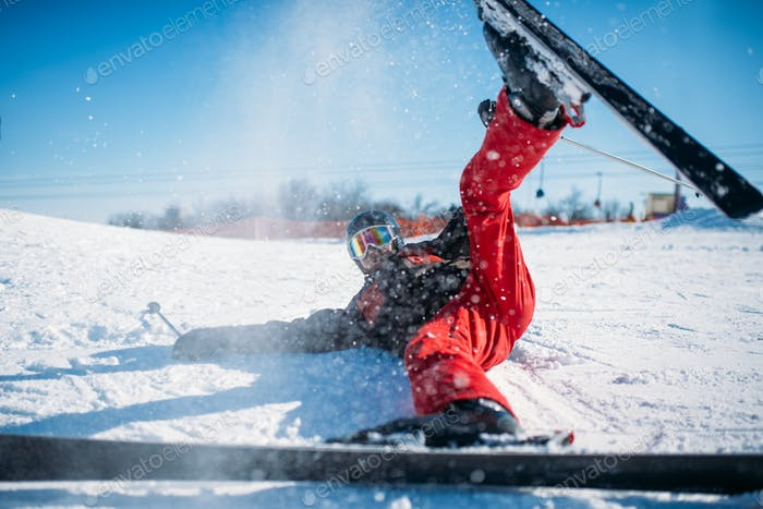 Skier in helmet and glasses lies on snowy mountain