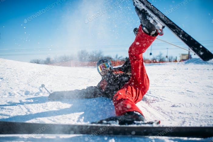 Skifahrer in Helm und Brille liegt auf verschneiten Bergen