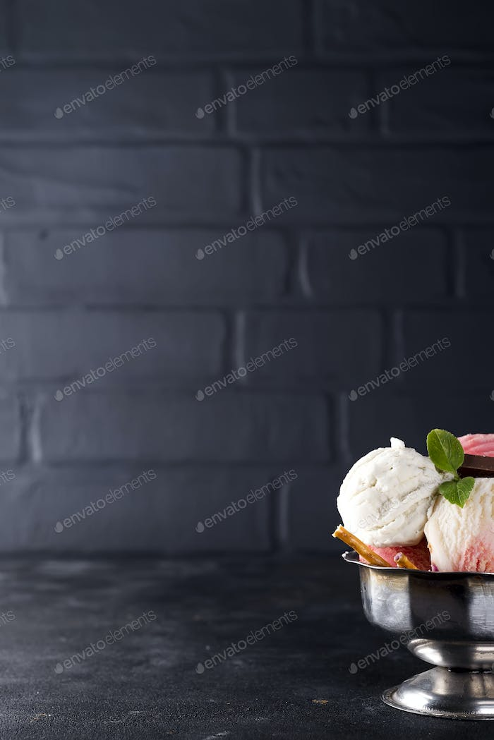 vanilla and pink ice cream in a bowl with frozen berries and waffle cone